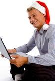 Glücklicher Mann mit Weihnachtshut und -laptop Stockfotos