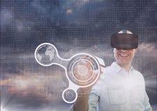 Glücklicher Mann in rührender Schnittstelle VR-Kopfhörers gegen purpurroten Himmel mit Wolken und Schnittstelle Stockfotos