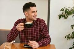 Glücklicher Mann-trinkender Kaffee im Café stockfoto