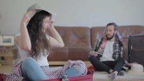 Gl?cklicher Mann und Frau auf dem Boden zu Hause, der einen Koffer vor Reise verpackt Die Frau, die im Koffer in sitzt stock footage
