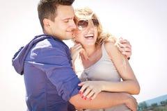 Glücklicher Mann und Frau, die draußen umfassend steht stockfoto