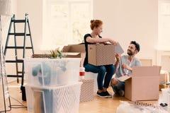 Glücklicher Mann und Frau, die Material von den Karikaturkästen beim Lieferung des Innenraums auspackt stockfotos