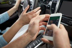 Glücklicher Mann und Frau mit dem Smartphone, der in Auto fährt Stockfotografie