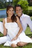 Glücklicher Mann und Frau verbinden draußen sitzen Stockfotografie