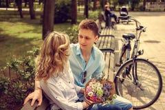 Glücklicher Mann und nette blonde Frau mit Blumen Stockfotografie