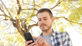 Glücklicher Mann unter Verwendung des intelligenten Telefons in einem Park