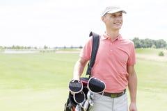 Glücklicher Mann von mittlerem Alter, der beim Tragen der Golftasche weg schaut Stockbild