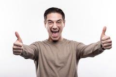 Glücklicher Mann von mittlerem Alter, der sich Daumen zeigt lizenzfreie stockbilder
