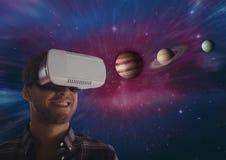 glücklicher Mann in VR-Kopfhörer, der Planeten 3D gegen Galaxiehintergrund betrachtet Stockbilder