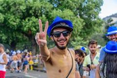 Glücklicher Mann in zwei Sonnenhüten, in der Sonnenbrille mit dem Schnurrbart und im Bart, der Friedenszeichen bei Bloco Orquestr Stockfoto