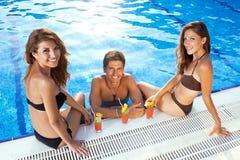 Glücklicher Mann zwischen zwei Frauen am Swimmingpool Stockfoto