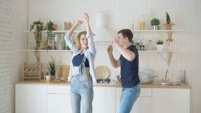 Glücklicher Mannfrauentanz durch gediente Tabelle in der modernen Küche stock video