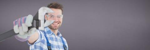 Glücklicher Mechanikermann, der einen Schlüssel gegen purpurroten Hintergrund hält Stockfotografie