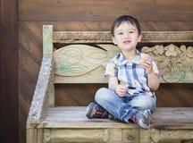 Glücklicher Mischrasse-Junge, der auf der Bank isst Sandwich sitzt Lizenzfreie Stockfotos