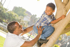 Glücklicher Mischrennen-Vater-helfender Sohn einen Baum steigen Lizenzfreie Stockfotos