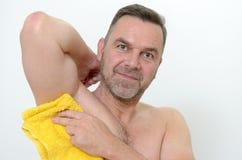 Glücklicher Mittelalter-Mann, der seine Achselhöhle mit Tuch trocknet Stockbild