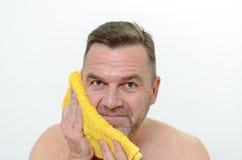 Glücklicher Mittelalter-Mann, der seine Backe mit Tuch trocknet Stockfoto