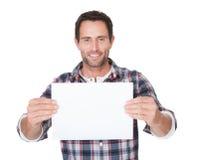 Glücklicher Mittelaltermann, der leeres Papier darstellt Stockfotografie