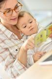 Glücklicher Moment für das Baby, das auf die Geschichte der Mutter hört Lizenzfreies Stockbild