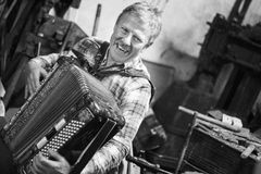 Glücklicher Musiker, der Akkordeon spielt lizenzfreies stockbild