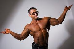 Glücklicher muskulöser Mann mit einem nackten Torso und lustigen Gläsern lizenzfreie stockbilder