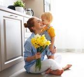 Glücklicher Mutter ` s Tag! Babysohn gibt flowersfor Mutter am Feiertag lizenzfreie stockfotografie
