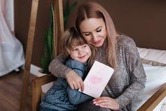 Glücklicher Mutter`s Tag Kindersohn beglückwünscht Mutter und gibt ihre Postkarte Mama und Sohn, die miling und umarmt worden sei lizenzfreie stockfotografie