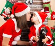 Glücklicher Mutter- und Kinderjunge, der gekleidetes Kostüm Santa Claus durch Kamin streichelt Weihnachten Lizenzfreies Stockbild