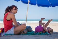 Glücklicher Mutter- und Mädchenunten Sonnenschirm am Strand Stockfotos