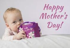 Glücklicher Muttertag Netter 8-monatiger Junge mit einem Geschenk in einer Tasche, die auf der weißen Decke liegt und Kamera betr Lizenzfreie Stockfotos