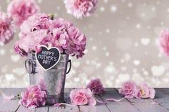 Glücklicher Muttertagesbuchstabe auf hölzernem Herzen und rosa Gartennelke blühen Stockfotografie