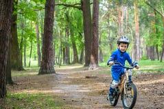 Glücklicher netter blonder Kinderjunge, der Spaß sein erstes Fahrrad auf sonnigem summ hat Lizenzfreie Stockfotografie
