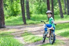 Glücklicher netter blonder Kinderjunge, der Spaß sein erstes Fahrrad auf sonnigem summ hat Stockbilder