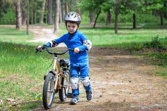 Glücklicher netter blonder Kinderjunge, der Spaß sein erstes Fahrrad auf sonnigem summ hat Lizenzfreie Stockfotos