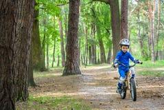 Glücklicher netter blonder Kinderjunge, der Spaß sein erstes Fahrrad auf sonnigem summ hat Stockfotografie