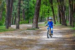 Glücklicher netter blonder Kinderjunge, der Spaß sein erstes Fahrrad auf sonnigem summ hat Lizenzfreies Stockbild