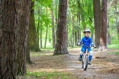 Glücklicher netter blonder Kinderjunge, der Spaß sein erstes Fahrrad am sonnigen Sommertag, draußen hat Kind, das Sport macht Akt Lizenzfreie Stockfotos
