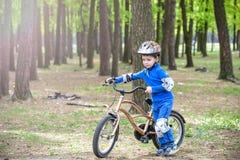 Glücklicher netter blonder Kinderjunge, der Spaß sein erstes Fahrrad am sonnigen Sommertag, draußen hat Kind, das Sport macht Akt Stockfotografie
