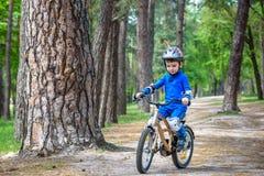Glücklicher netter blonder Kinderjunge, der Spaß sein erstes Fahrrad am sonnigen Sommertag, draußen hat Kind, das Sport macht Akt Lizenzfreie Stockfotografie