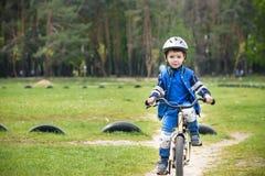 Glücklicher netter blonder Kinderjunge, der Spaß sein erstes Fahrrad am sonnigen Sommertag hat Lizenzfreie Stockbilder