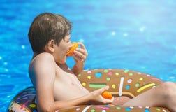 Glücklicher netter Jugendlicher des kleinen Jungen, der auf aufblasbarem Donutring mit Orange im Swimmingpool liegt Aktive Spiele stockbild