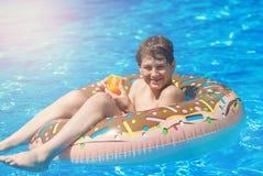 Glücklicher netter Jugendlicher des kleinen Jungen, der auf aufblasbarem Donutring mit Orange im Swimmingpool liegt Aktive Spiele lizenzfreie stockfotos