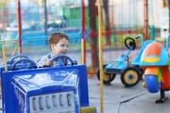 Glücklicher netter kleiner Junge fährt auf Auto des Karussells Lizenzfreie Stockbilder