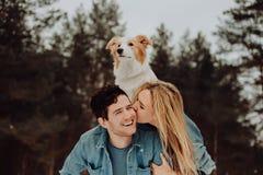 Glücklicher netter lächelnder Mann mit Mädchen und Hund auf seinem zurück Küssen von Paaren von jungen Leuten in den Denimklagen  stockbilder