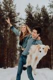 Glücklicher netter lächelnder Mann mit Mädchen und Hund auf seinen Händen Paare von jungen Leuten in den Denimklagen im schneebed stockfotografie