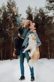 Glücklicher netter lächelnder Mann mit Mädchen und Hund auf seinen Händen Paare von jungen Leuten in den Denimklagen im schneebed stockbild