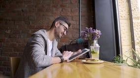 Glücklicher netter männlicher Student, der Tablet-Computer verwendet Kerl, der in einem Café mit einer Tablette in ihren Händen s stock video