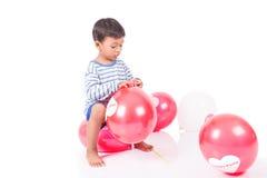Glücklicher netter Spielrotballon des kleinen Jungen Stockbild