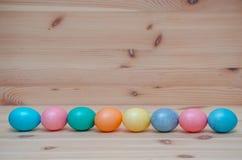 Glücklicher Ostereipastell gefärbt auf dem hölzernen Stockbilder