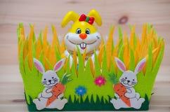 Glücklicher Osterhase in einem Korb mit Gras und Stockbild
